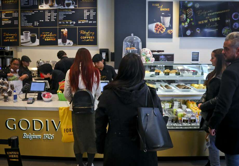 Customers wait in line for service at Godiva's new cafe in New York, Tuesday April 16, 2019. Godiva, the private Belgium chocolate maker, is looking beyond its iconic gold gift box of chocolates. The confectioner is rolling out 2,000 cafes that will serve a complete menu of items like the croiffle, a croissant and waffle hybrid. (AP Photo/Bebeto Matthews) Photo: Photos By Bebeto Matthews / Associated Press