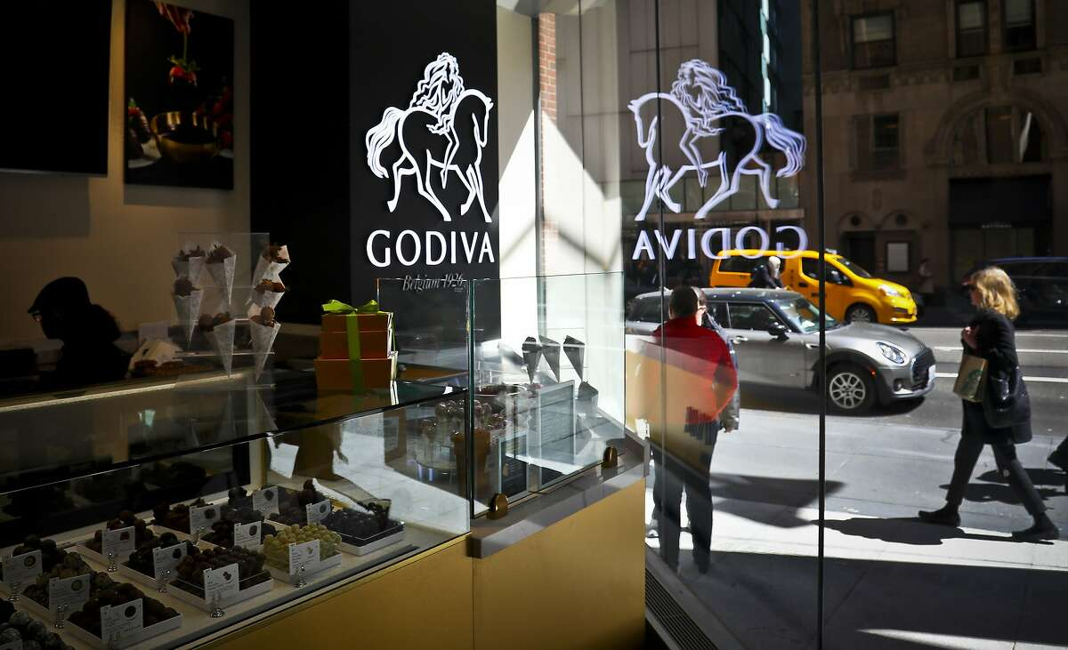 A display of chocolate treats is displayed at Godiva's new cafe in New York, Tuesday April 16, 2019.  The news comes less than two years after Godiva's planned expansion of 2,000 cafes around the globe by 2025. Americans won't be short on Godiva chocolates, though. The products will continue to be sold online, in grocery stores and other retailers that carry their products. In a statement, Godiva said in-person shopping