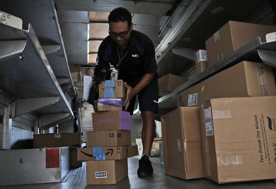 FILE - In this July 17, 2018, file photo, a FedEx employee delivers packages in Miami. Outside of ditching online shopping altogether, there are some small tweaks in how you shop that can cut down on the impact on the environment, such as slowing down shipping times and not filling up the cart with stuff you know you won't keep. (AP Photo/Lynne Sladky, File) Photo: Lynne Sladky, Associated Press
