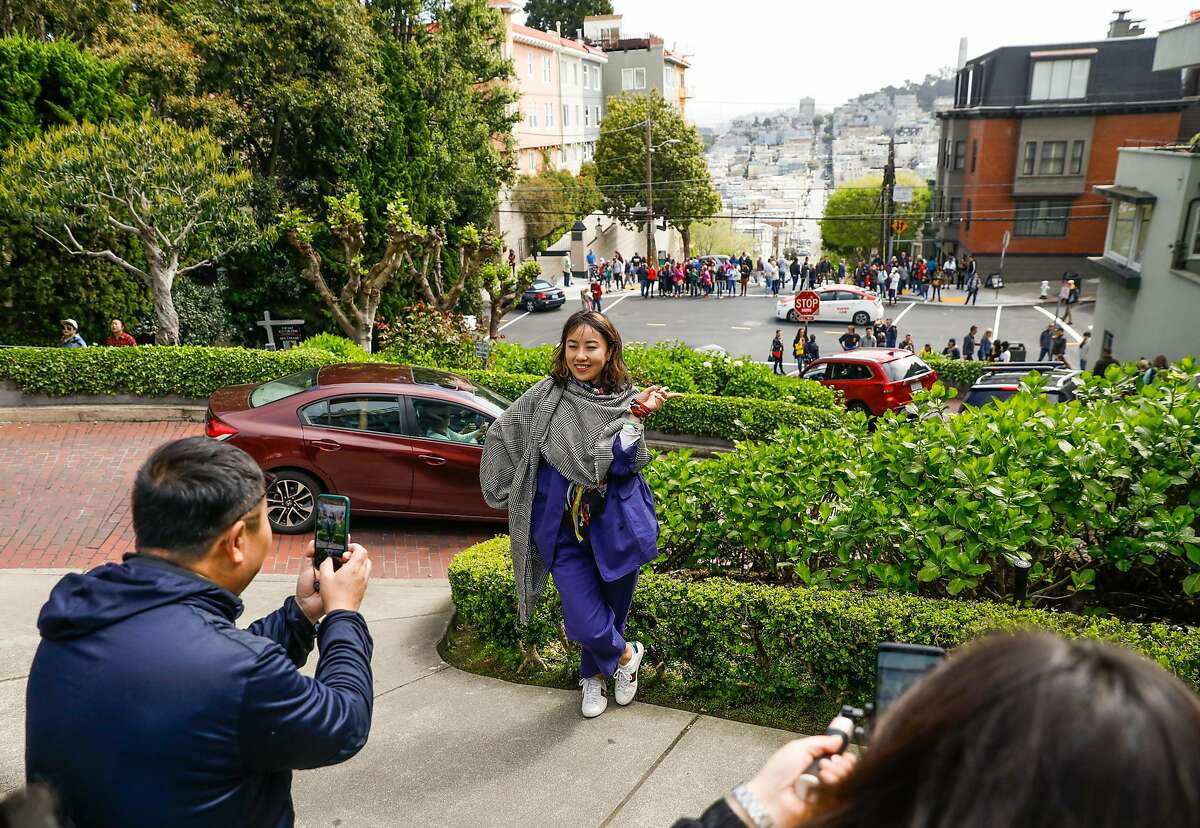 Ada Xu (center), who is visitng from China, gets photographed while visiting Lombard Street in San Francisco, California, on Sunday, April 14, 2019.