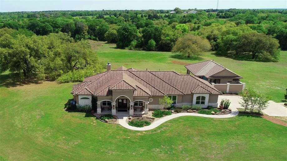 Located at 10000 FM 389 in Brenham, this 78-acre mega-ranch features a three bedroom, three bathroom Tuscany-style house complete with its own infinity pool and campsite. Located next to a one-and-a-half acre stocked pond, the camp features one main building with a kitchen and dining space, multiple cabins, gazebo, fire pit area and sundecks. Multiple trails to spring-fed streams and waterfalls are also found throughout the property. Photo: Houston Association Of Realtors