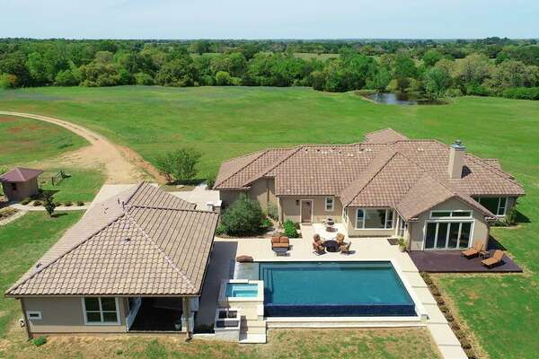 Located at 10000 FM 389 in Brenham, this 78-acre mega-ranch features a three bedroom, three bathroom Tuscany-style house complete with its own infinity pool and campsite. Located next to a one-and-a-half acre stocked pond, the camp features one main building with a kitchen and dining space, multiple cabins, gazebo, fire pit area and sundecks. Multiple trails to spring-fed streams and waterfalls are also found throughout the property.