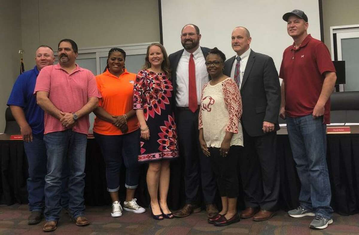 Crosby High School hired Jerry Prieto (center, red tie) as its new head football coach on Tuesday, April 16, 2019. Prieto posed for a photo with his wife (to his right) and the Crosby ISD school board after his hiring was made official.