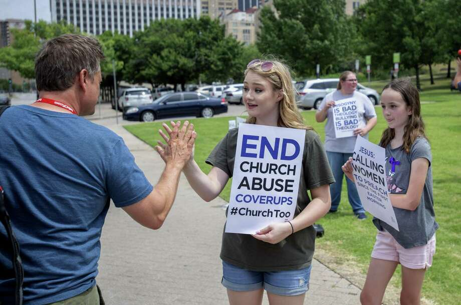 Claire Summers, 16, gets a high five as she and her sister Ella Summers, 10, right, protest the Southern Baptist Convention's treatment of women June 12 outside the convention's annual meeting at the Kay Bailey Hutchison Convention Center in Dallas. The Houston Chronicle and San Antonio Express-News reported that hundreds of Southern Baptist clergy and staff had been accused of sexual misconduct over the past 20 years. Legislation could help. Photo: Jeffrey McWhorter /Associated Press / FR170451 AP