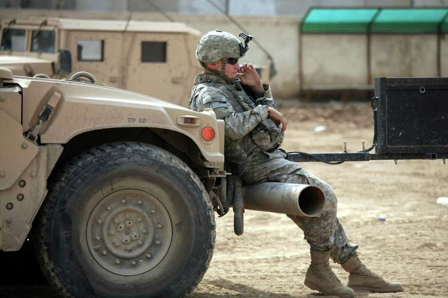 March 8, 2007, U.S. Army Pvt. John Wertsch, 21, from Cold Spring, Minn., of the 2nd Battalion, 325th Airborne Infantry Regiment, takes a cigarette break at a combat outpost in Baghdad, Iraq. Smoking rates in the military are higher than the general population of smokers. Photo: MAYA ALLERUZZO /AP / AP