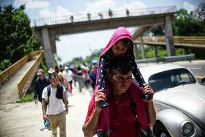 Central American migrants heading in caravan to the US rest beside the road between Metapa and Tapachula in Mexico on April 12. They do not, as the president essentially charges, pose an existential threat.