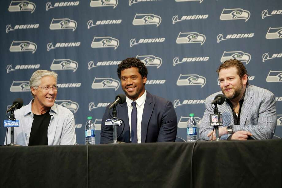 Seahawks quarterback Russell Wilson is flanked by head coach Pete Carroll and general manager John Schneider at a press conference, Wednesday, discussing Wilson's just signed, four  year contract extension, which makes him the highest-paid player in the NFL, April 17, 2019.  So how does that money look if he were to put it all into real estate? A very expensive memory lane, but not necessarily a fruitless one. Click through to see    (Genna Martin, Seattlepi.com) Photo: Genna Martin, Genna Martin/Seattlepi / SEATTLEPI