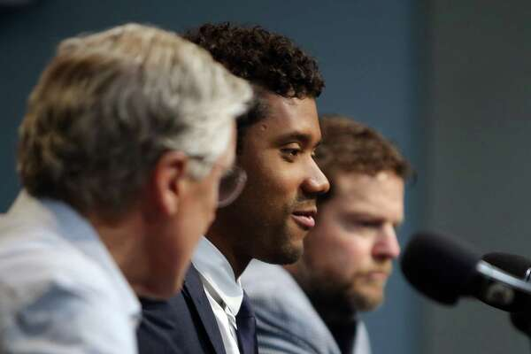 Seahawks quarterback Russell Wilson is flanked by head coach Pete Carroll and general manager John Schneider at a press conference, Wednesday, discussing Wilson's just signed, four year contract extension, which makes him the highest-paid player in the NFL, April 17, 2019. (Genna Martin, Seattlepi.com)