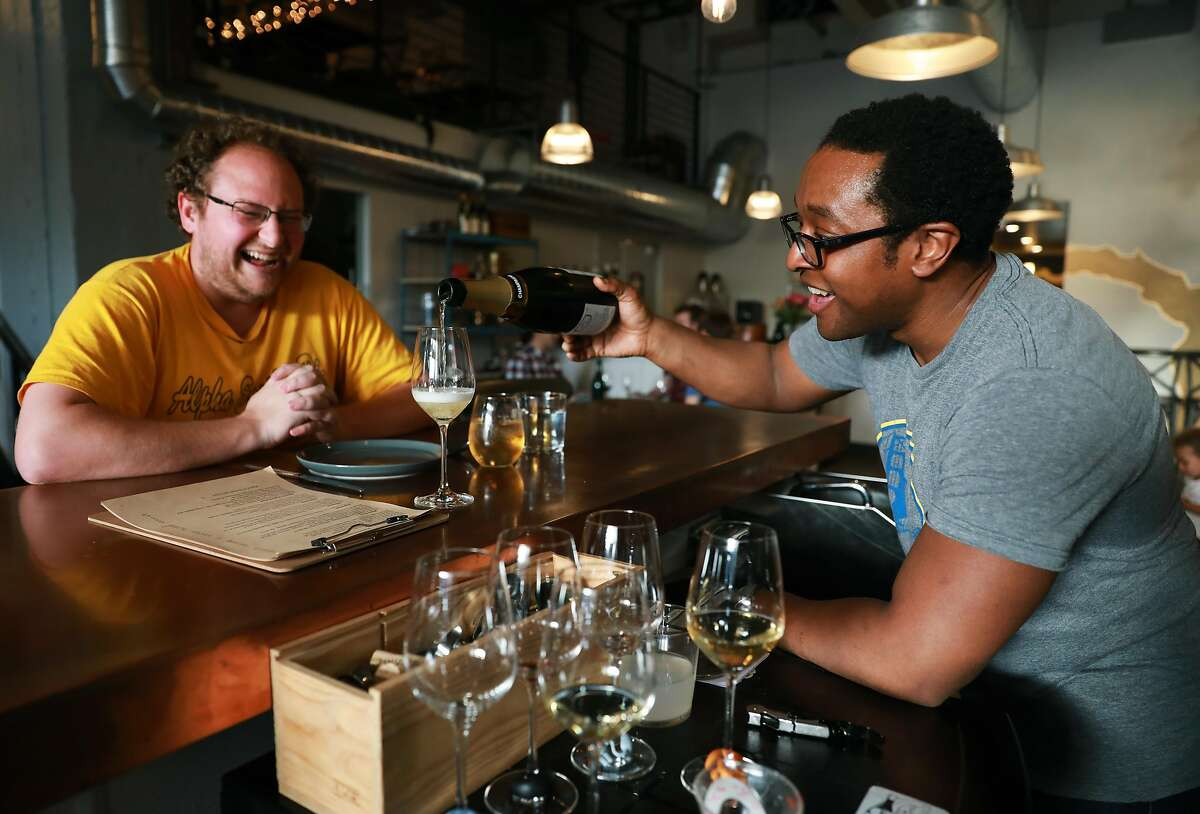 Andy Copeland (left) watches Chris Gaither pour a glass of champagne at Ungrafted, a wine bar located at 2419 3rd St., in San Francisco, Calif., on Wednesday, April 10, 2019. Gaither and his wife Rebecca Fineman are co-owners of the new establishment.