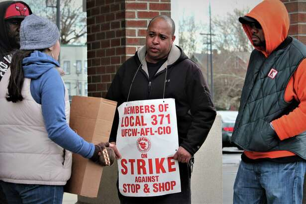 Kevin Hall, center, of New Haven, pickets Monday at the city Stop & Shop store where he's worked for five years.