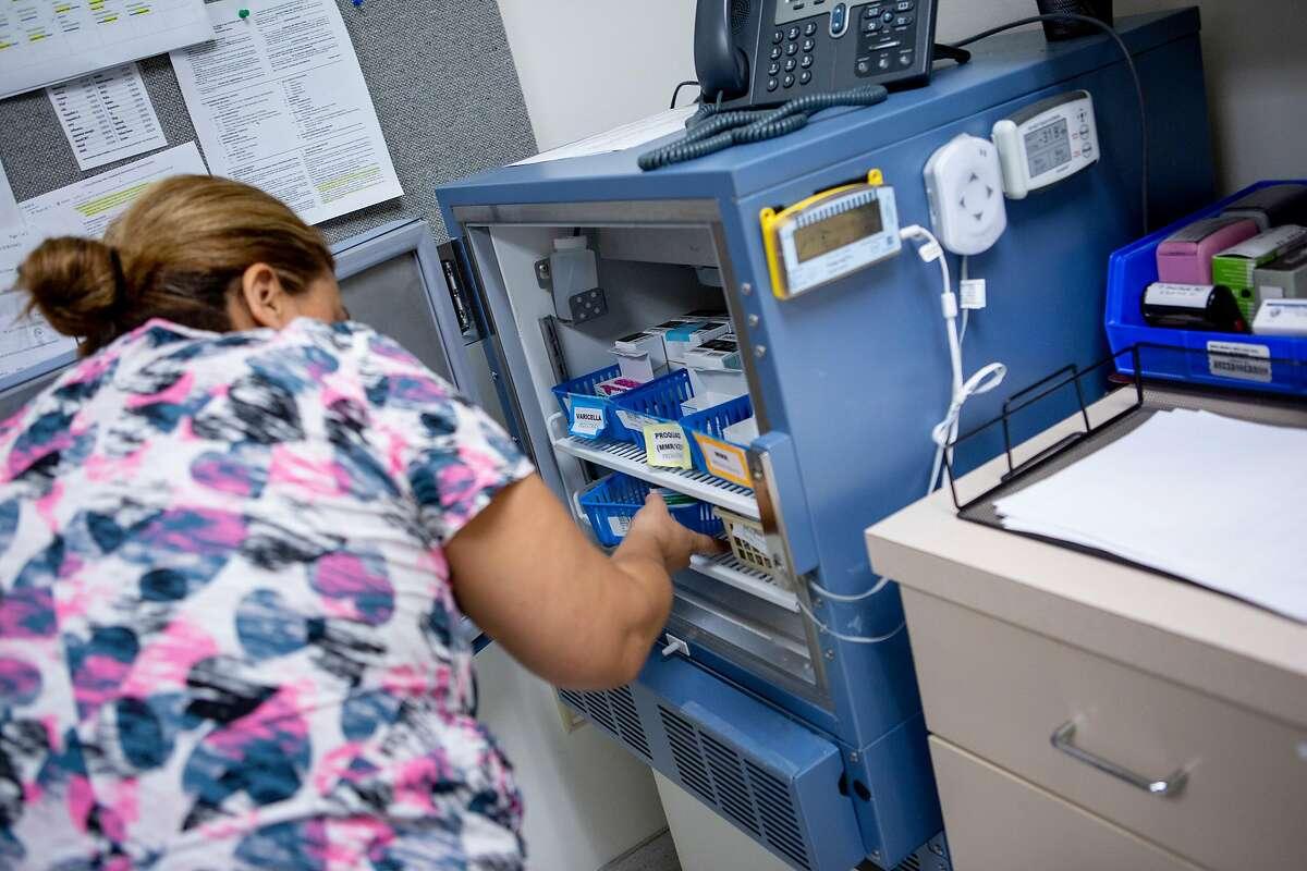 LVN Sara Gaytan prepares the MMR vaccine for Carmen Sanchez at Kaiser Permanente Redwood City on Wednesday, April 17, 2019.