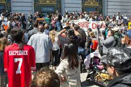 People stand outside of City Hall, holding signs during a rally in support of the new proposal to close San Francisco juvenile hall. On Tuesday, April 9, 2019. San Francisco, Calif.