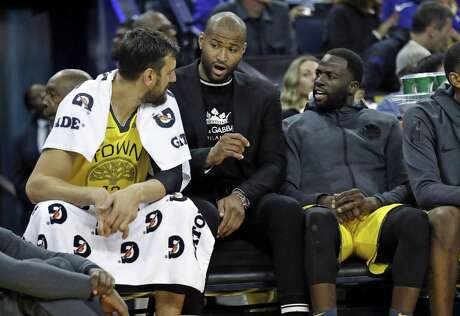 Golden State Warriors' DeMarcus Cousins talks with Andrew Bogut and Draymond Green in March game against the Pistons.