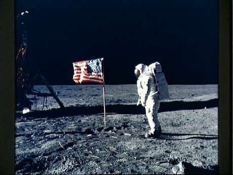 Astronaut Edwin E. Aldrin Jr., lunar module pilot, poses for a photograph beside the deployed United States flag during Apollo 11's extravehicular activity on the lunar surface. This picture was taken by mission commander Neil A. Armstrong.