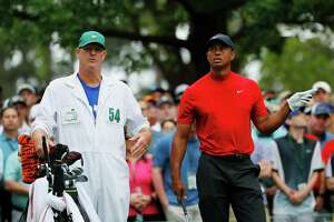 Tiger Woods waits with caddie Joe LaCava on the fourth hole during the final round of the Masters at Augusta National Golf Club on Sunday in Augusta, Ga.