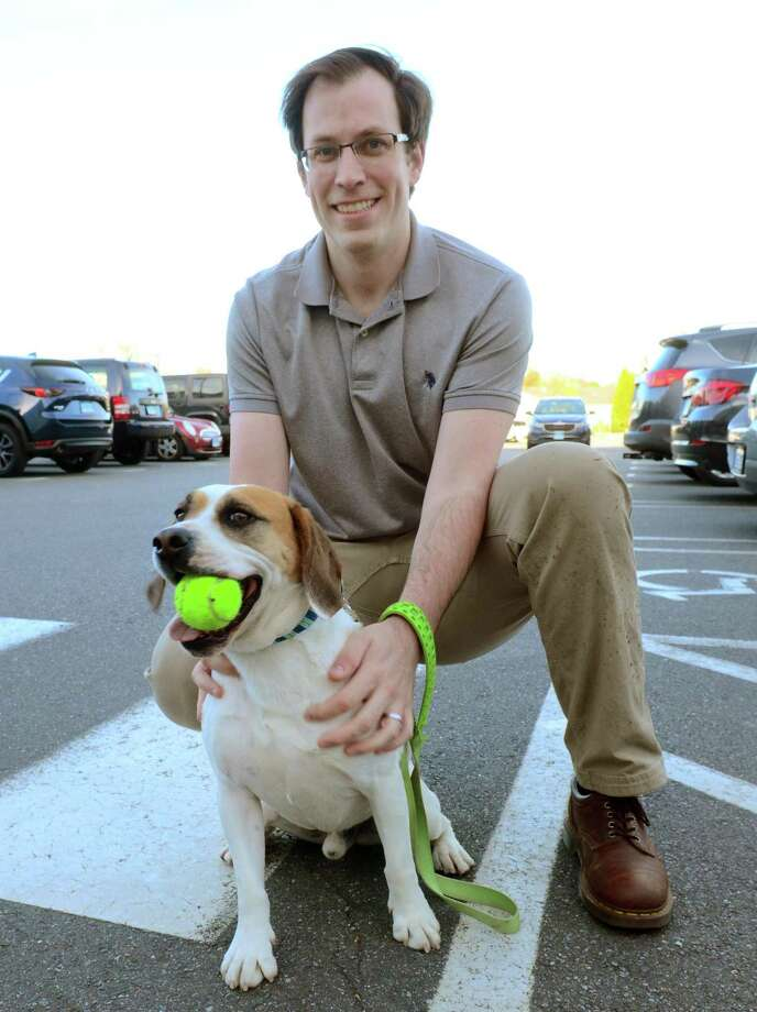 Ryan McGuire of Orange poses with his dog Nigel, who took top honors in the New Haven Register's Pet Madness contest, in front of ShopRite in Milford Wednesday.  McGuire and his wife, Jenna, chose the Fidelco Guide Dog Association as the recipient of the $150 donation from ShopRite. And in lieu of them receiving a ShopRite gift card in the same amount, they requested ShopRite instead donate the $150 to the Connecticut Food Bank. Photo: Christian Abraham / Hearst Connecticut Media / Connecticut Post