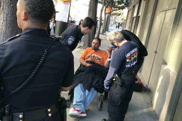 A man is treated for a slash wound on the wrist after an altercation in San Francisco on April 17, 2019.