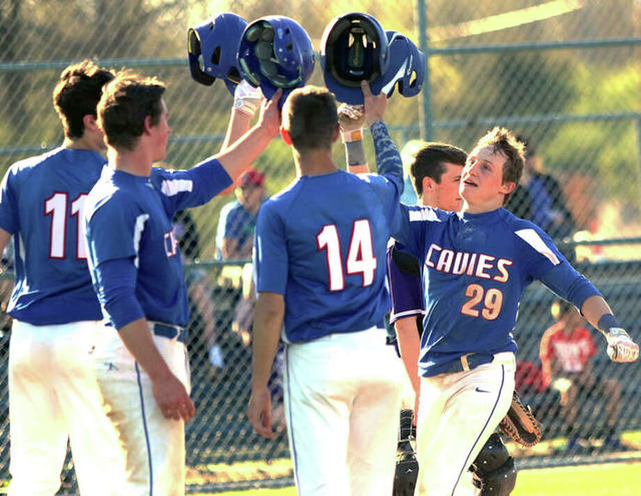 Carlinville's Aidan Naugle (29) is greeted at the plate after his grand slam drove home Sam Tieman (11), Colton DeLong and Lonny Rosentreter in the fourth inning of the Cavaliers' five-inning victory Tuesday at Litchfield. Photo: Greg Shashack | The Telegraph