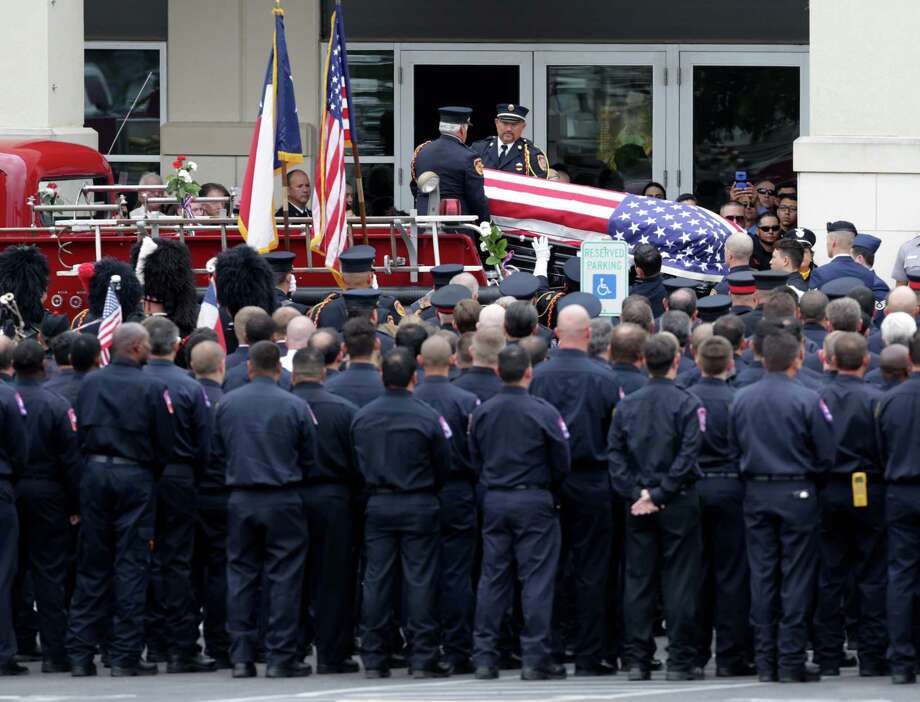 Firefighters salute as the body of a fallen firefighter arrives at Community Bible Church for the funeral for firefighter Scott Deem, who was killed May 18 fighting a blaze on the Northwest side of town, on Friday, May 26, 2017. Photo: Bob Owen, Staff / San Antonio Express-News / San Antonio Express-News