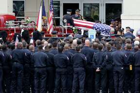 Firefighters salute as the body of a fallen firefighter arrives at Community Bible Church for the funeral for firefighter Scott Deem, who was killed May 18 fighting a blaze on the Northwest side of town, on Friday, May 26, 2017.