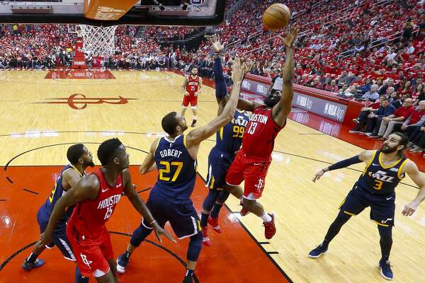 Houston Rockets guard James Harden (13) shoots over Utah Jazz center Rudy Gobert (27) and forward Jae Crowder (99) during the first half of game 2 during the NBA playoffs at the Toyota Center in Houston, Wednesday, April 17, 2019.