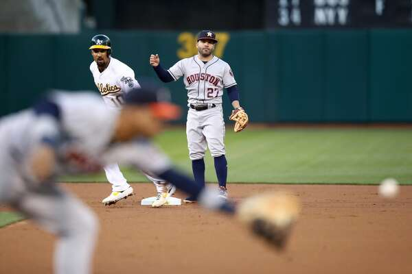 OAKLAND, CALIFORNIA - APRIL 17: Jose Altuve #27 of the Houston Astros throws wide to first base as he tried to turn a double play after Marcus Semien #10 of the Oakland Athletics was forced out at second base in the first inning at Oakland-Alameda County Coliseum on April 17, 2019 in Oakland, California. (Photo by Ezra Shaw/Getty Images)