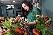 """Liz Mally, who owns LPF Blooms, works on a centerpiece in her studio in her basement in Ferndale, Michigan. Mally learned there is misery in doing work purely for the sake of building a portfolio. """"I was taking on pretty much any client I could get, regardless of budget or style, in hopes of gaining experience and getting my name out there,"""" Mally said."""