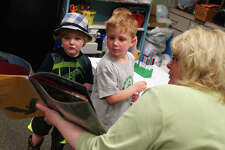 """Noah Eyth (left), 2, and Nicholas Warmowski, 5, color paper bats Wednesday at Jacksonville Public Library as library clerk Diane Hequet reads the book """"Bats at the Library"""" during Story Hour. Wednesday was National Bat Appreciation Day and the library joined in the celebration."""