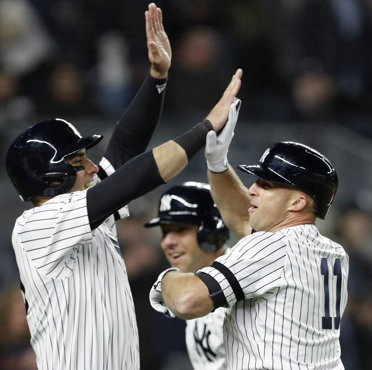 New York Yankees Brett Gardner (11) celebrates with the Yankees Mike Tauchman, left, and Austin Romine, center, after hitting a seventh-inning grand slam in baseball game against the Boston Red Sox, Wednesday, April 17, 2019, in New York. (AP Photo/Kathy Willens)