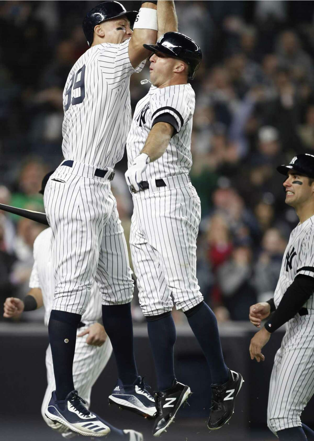 New York Yankees Mike Tauchman, right, watches as New York Yankees center fielder Brett Gardner (11) and Yankees on-deck batter Aaron Judge celebrate Gardner's seventh-inning, grand slam in a baseball game against the Boston Red Sox, Wednesday, April 17, 2019, in New York. (AP Photo/Kathy Willens)