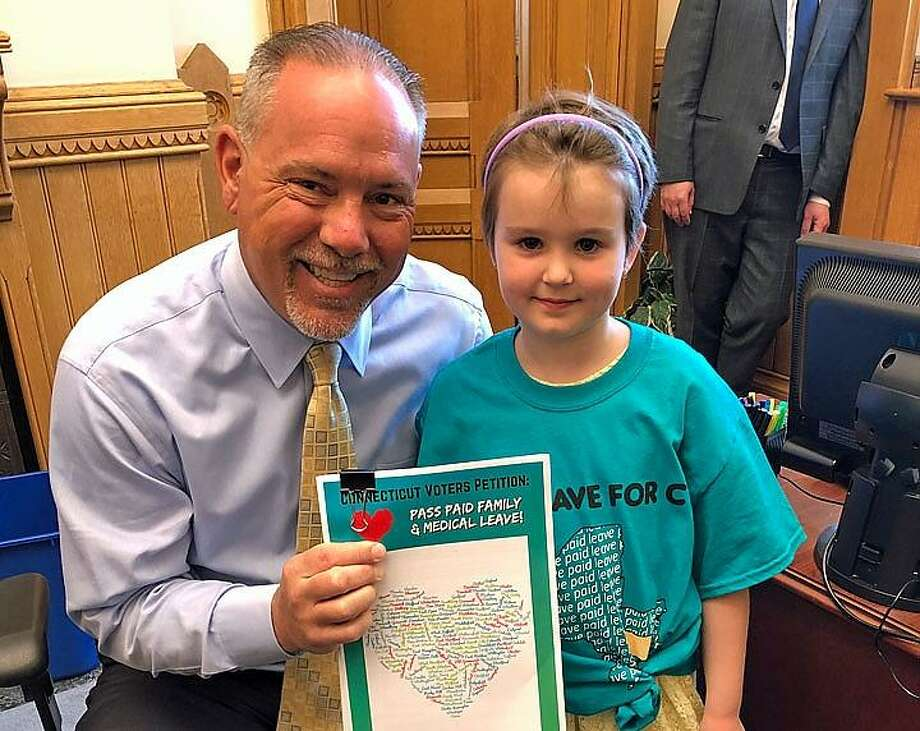 House Speaker Joe Aresimowicz with 7-year-old Winnie who delivered a letter signed by more than 5,000 people in support of paid family leave. Photo: Contributed Photo