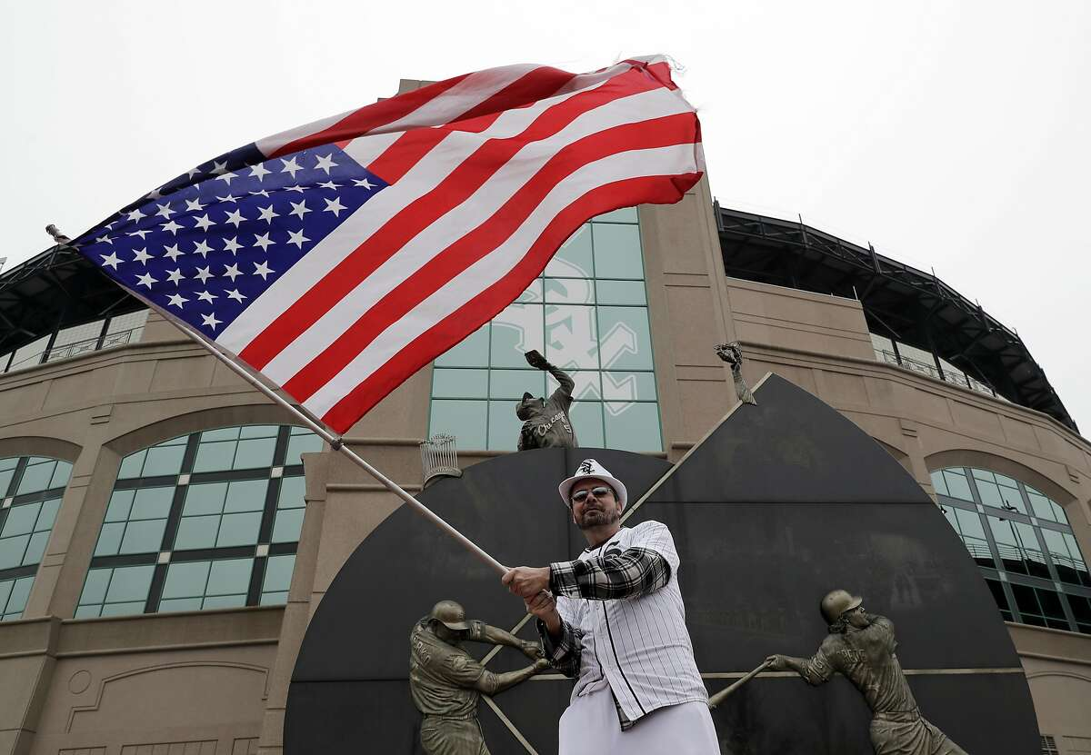 Bob Hunt waves an American flag outside of Guaranteed Rate Field before the Chicago White Sox home opening baseball game against the Seattle Mariners, Friday, April 5, 2019, in Chicago. (AP Photo/Nam Y. Huh)