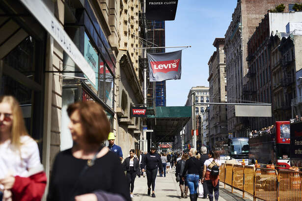 Shoppers and pedestrians pass in front of a Levis Strauss store in the SoHo neighborhood of New York on March 30, 2019.