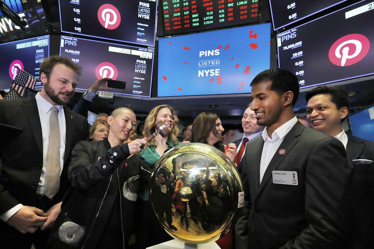 Pinterest co-founder and chief product officer Evan Sharp, left, and fellow co-founder & CEO Ben Silbermann, right, watch as company Communications Manager Enid Huang rings a ceremonial bell when their IPO begins trading on the New York Stock Exchange floor, Thursday, April 18, 2019. (AP Photo/Richard Drew)