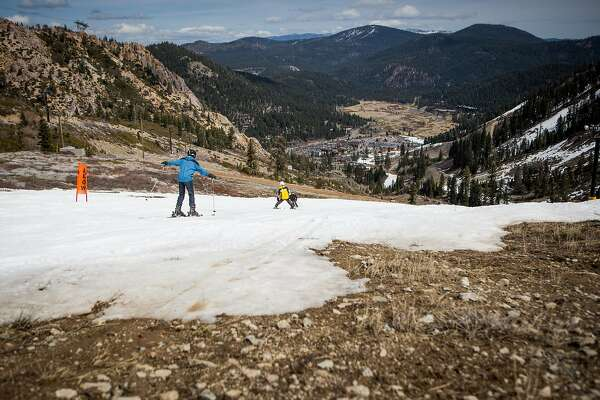 Skiers thread their way through patches of dirt at Squaw Valley Ski Resort, March 21, 2015 in Olympic Valley, California. Many Tahoe-area ski resorts have closed due to low snowfall as California's historic drought continues.