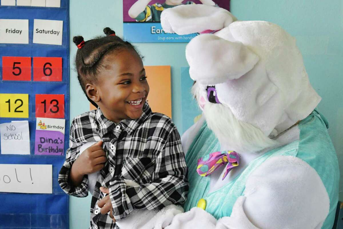 Preschool student, Gayla Stover-Parson, sits on the lap of the Spring Bunny who visited the children at Unity House's A Child's Place in celebration of springtime on Thursday, April 18, 2019, in Albany, N.Y. The children had their photo taken with the Spring Bunny and received a book. (Paul Buckowski/Times Union)