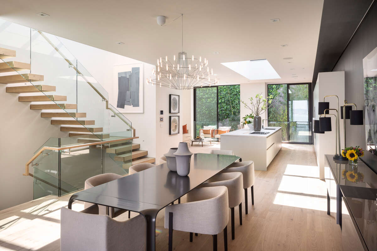 The open kitchen is anchored by marble-topped island with a sculptured beveled edge and rests beneath a skylight.