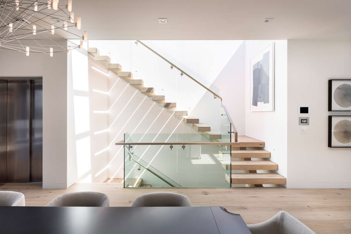 An architectural staircase with floating tread leads to the roof deck.