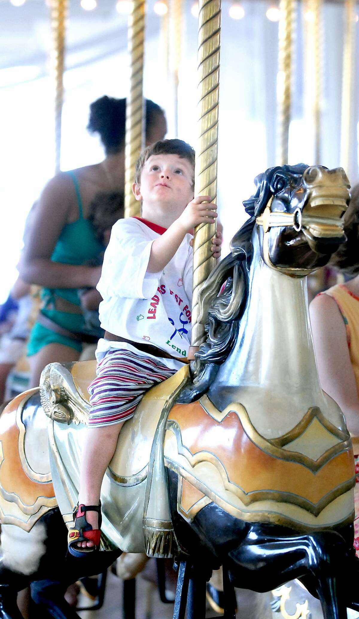 A child rides the carousel at Lighthouse Point Park in New Haven during a Lead Awareness Picnic.