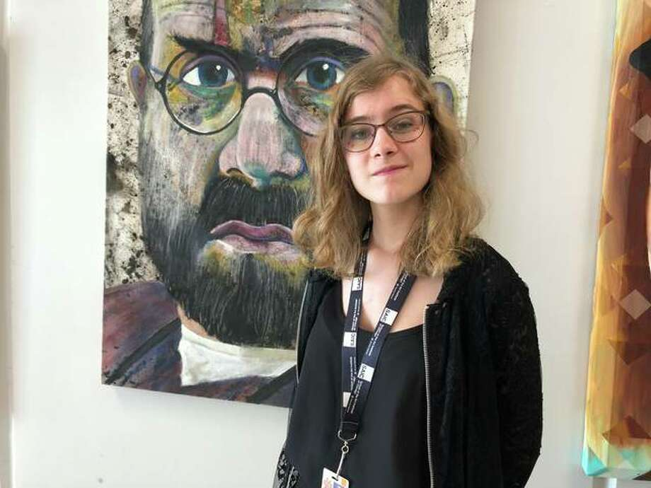 EHS Senior Kia Smidt stands in front of a Dennis DeToye painting hanging in the high school. Smidt is the first EHS student awarded the Dennis DeToye Art Scholarship. Photo: Julia Biggs | The Intelligencer