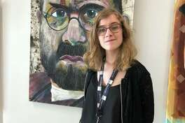 EHS Senior Kia Smidt stands in front of a Dennis DeToye painting hanging in the high school. Smidt is the first EHS student awarded the Dennis DeToye Art Scholarship.