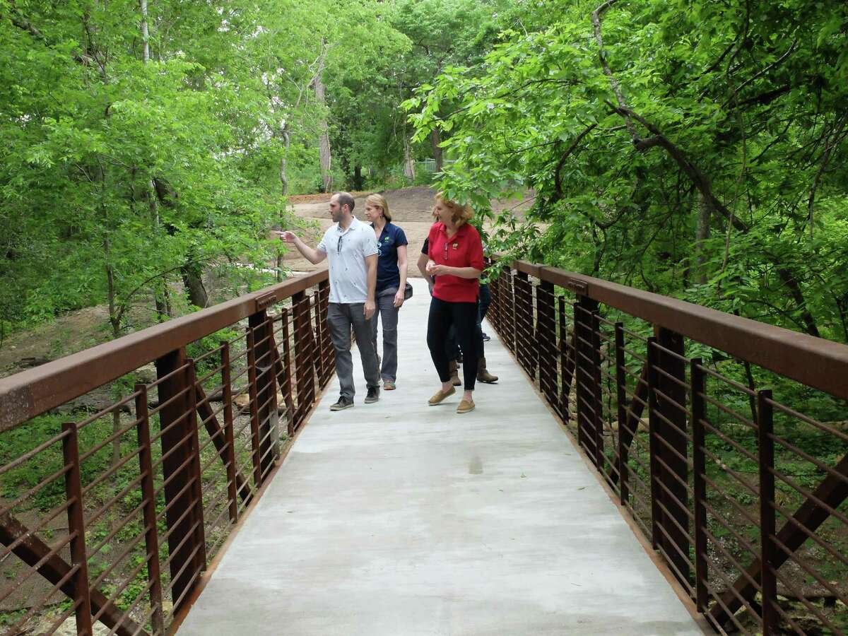 Conners Ladner of Design Workshop, from left, conservation director Emily Manderson, executive director Debbie Markey and other staff of the Houston Arboretum & Nature Center cross one of two new steel bridges across the arboretum's new ravine path.