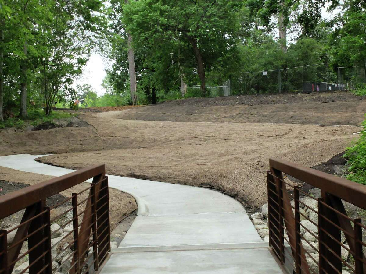While much of the new ravine trail at the Houston Arboretum & Nature Center is covered with a soft layer of mulch that can easily be replaced after rain, an ADA-accessible concrete switchback leads to the first bridge. Seeding mesh to support new plantings covers the ground toward the parking lot.