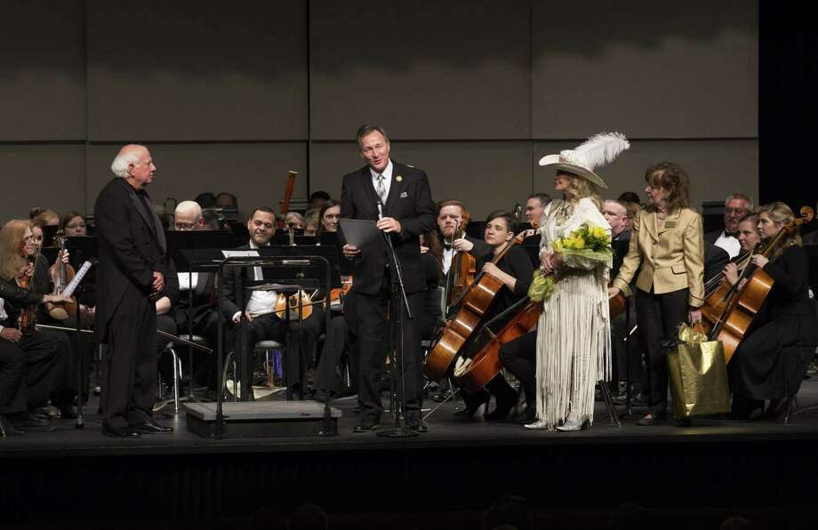 Conroe City Councilman Ray McDonald, center, reads a proclamation from the City of Conroe for Dr. Don Hutson, retiring conductor of the Conroe Symphony Orchestra at a farewell performance on April 13 at Conroe High School. Symphony Friends representatives Lyn Howard and Judge Kathleen Hamilton presented Hutson with flowers and a special gift upon his retirement. Photo: Photo By Brad Meyer