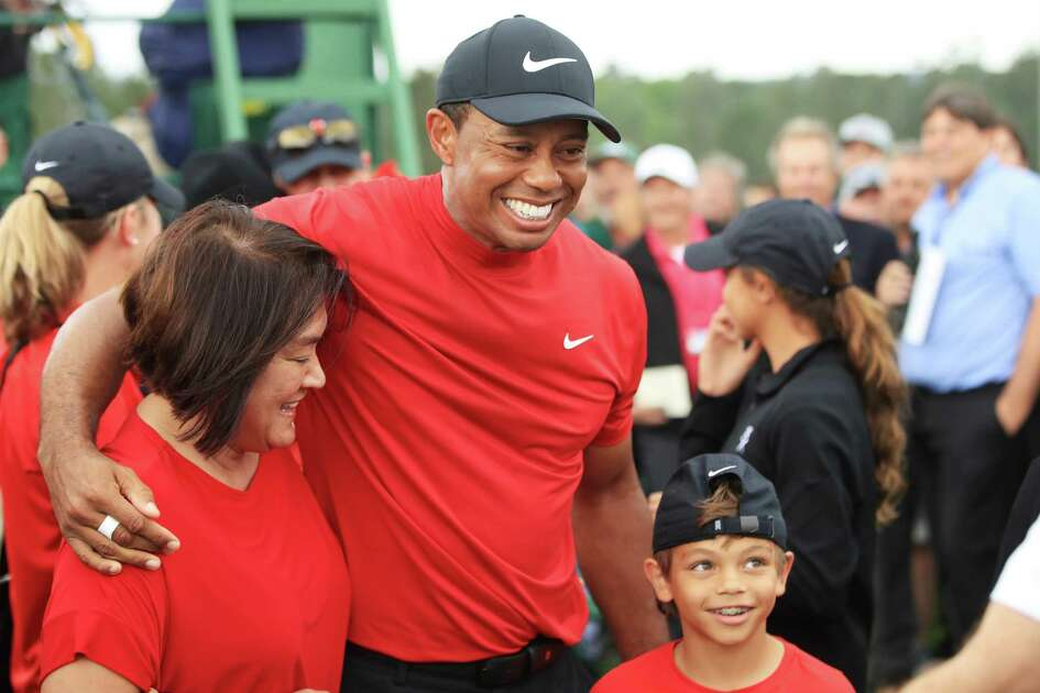 AUGUSTA, GEORGIA - APRIL 14: Tiger Woods of the United States celebrates with his son Charlie Axel as he comes off the 18th hole in honor of his win during the final round of the Masters at Augusta National Golf Club on April 14, 2019 in Augusta, Georgia.