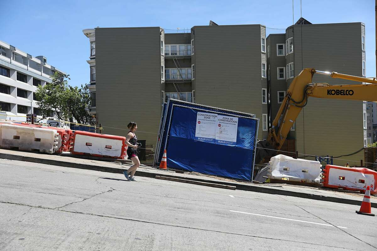 A person jogging runs past a construction site on Gough Street near Eddy Street on Thursday, April 18, 2019 in San Francisco, Calif.