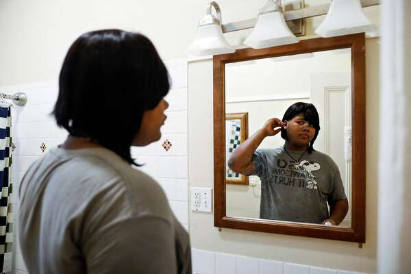 A trans woman named Kat Blackburn looks in the mirror after brushing her teeth at her home in San Francisco, California, on Wednesday, April 17, 2019. Kat lives in one of the first shelter-transitional housing programs in the United States for transgender youths in San Francisco.