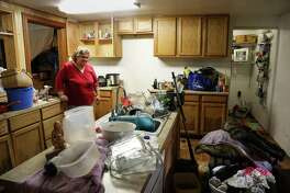 "Hazel Smith looks at her flooded kitchen Saturday, May 28, 2016, in Tomball. The home, which sits at least two feet off the ground, had at least two feet of water in it the night before. ""I've been staying with neighbors I'd never met before the flood,"" she said. ""I honestly don't care about the material things, but it's all that hard work."" Smith said she works two jobs. ( Jon Shapley / Houston Chronicle )"