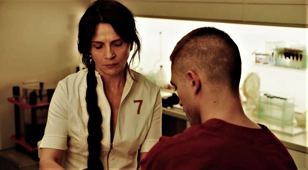 This image released by A24 Films shows Juliette Binoche, left, and Robert Pattinson in a scene from