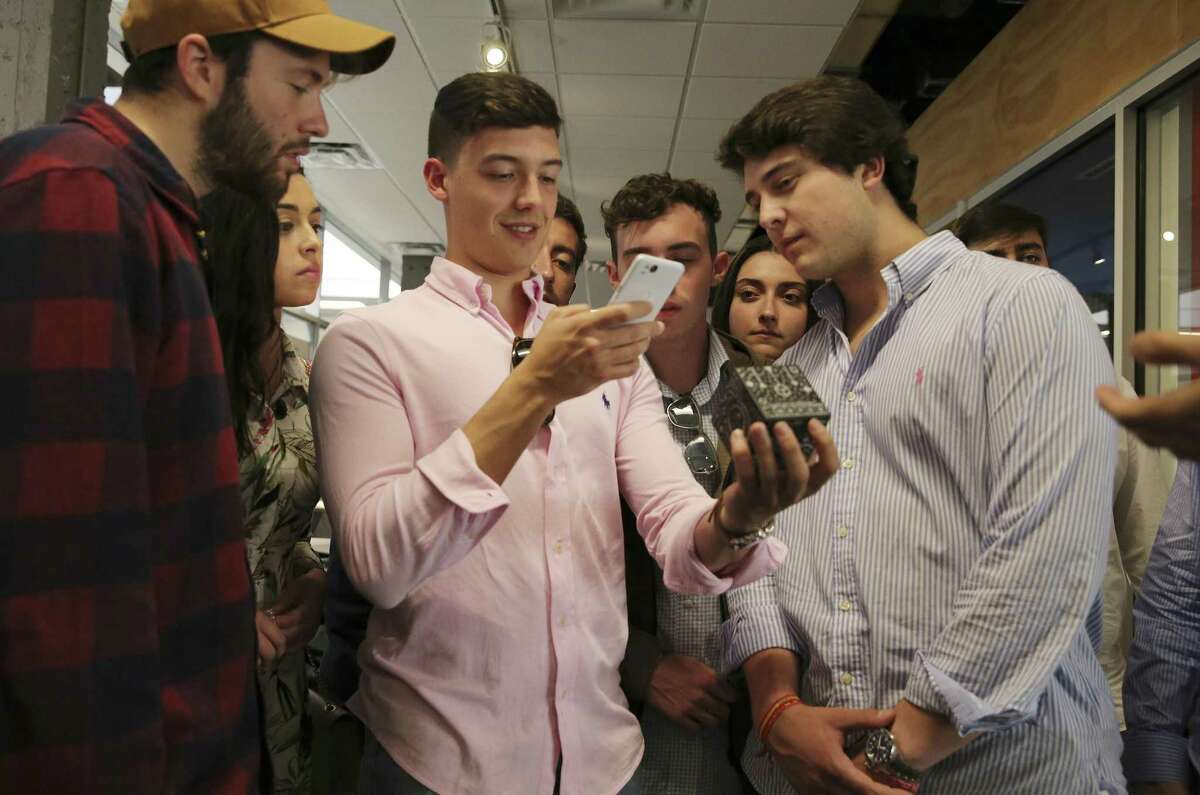 """Students Martin Ignacio (from right), Alonso Pedro and Camilo Fernandez show fellow students from Universidad Pontifica de Salamanca in Spain how an augmented reality cube works during a tour of Geekdom on Thursday, Apr. 18, 2019. They are on their first Reciprocal Visit with Trinity University, a weeklong trip to San Antonio to learn about the city, American politics and immigration. On Thursday, the students had a lecture with Mariela Jasso, who works for RAICES, about """"the immigration situation in South Texas"""" and visited the Velocity Texas Business Incubator and Geekdom. Trinity students visited Salamanca this fall, and """"invited their Spanish hosts to visit here,"""" where they've seen City Council, the Alamo and learned about San Antonio's history. (Kin Man Hui/San Antonio Express-News)"""